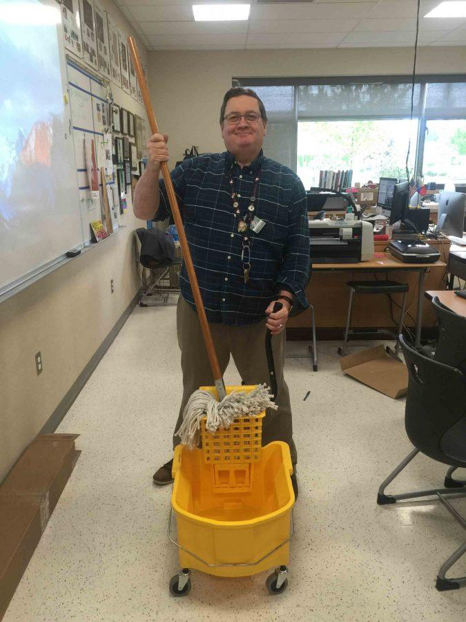 New CTE teacher Thomas Kaup proudly shows his new mop and bucket for the Silkscreen Room.